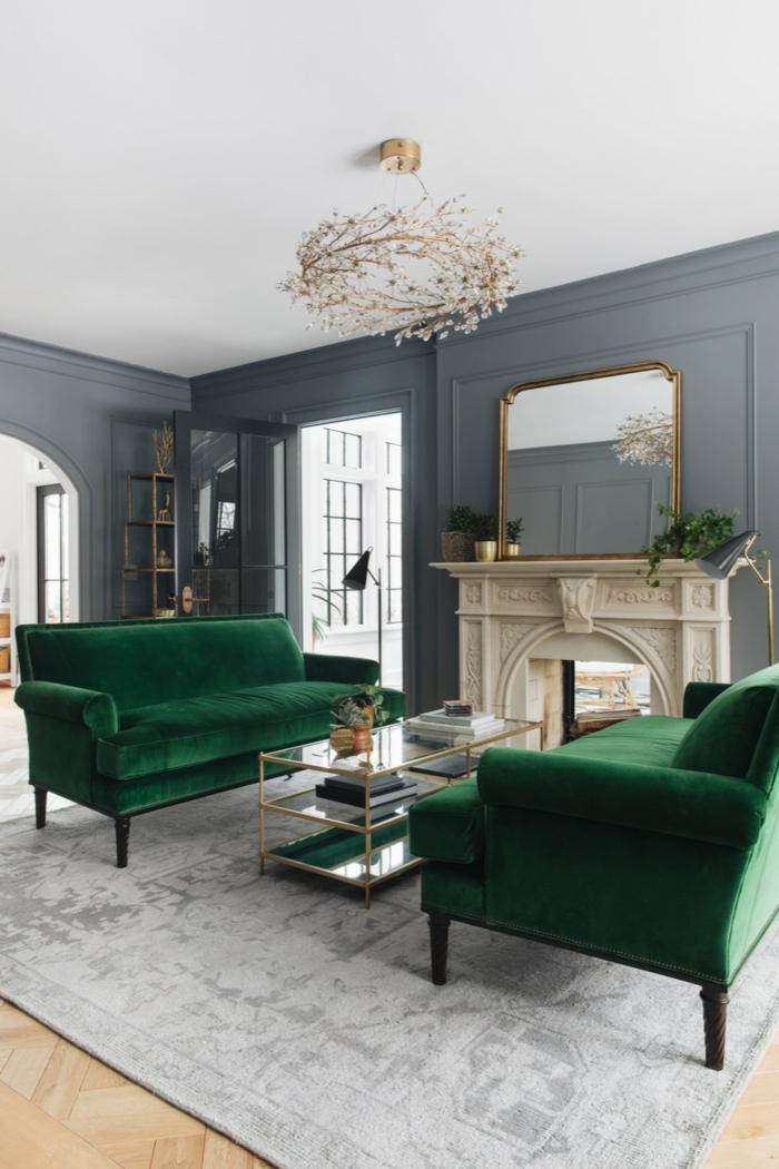 Luxuriöse Inneneinrichtung, Sofa in grün, graue Wand, Kamin und Spiegel, Wohnzimmer einrichten beispiele