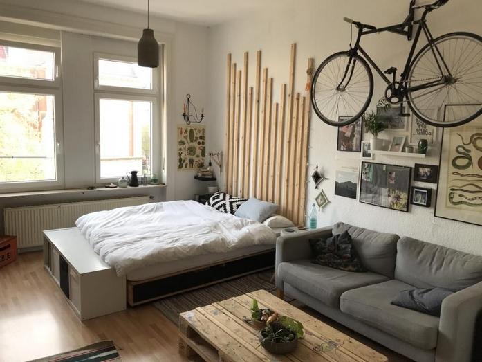 1 zimmer wohnung einrichten 30qm bett im wohnzimmer sofa fahrrad hängen licht