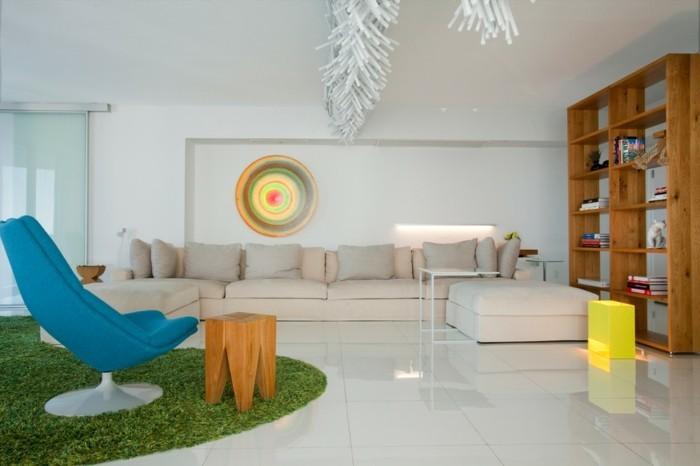 1wandnische-kunst-im-wohnzimmer-blauer-stuhl-gruner-pluschteppich-hocker-aus-holz-glaswand