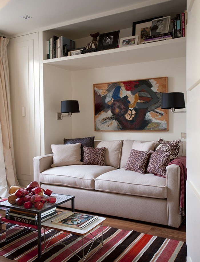 White spare room with cream sofa bed, selection of cushions, coffee table, art art books, abstract painting H&G 09/2011 pub orig