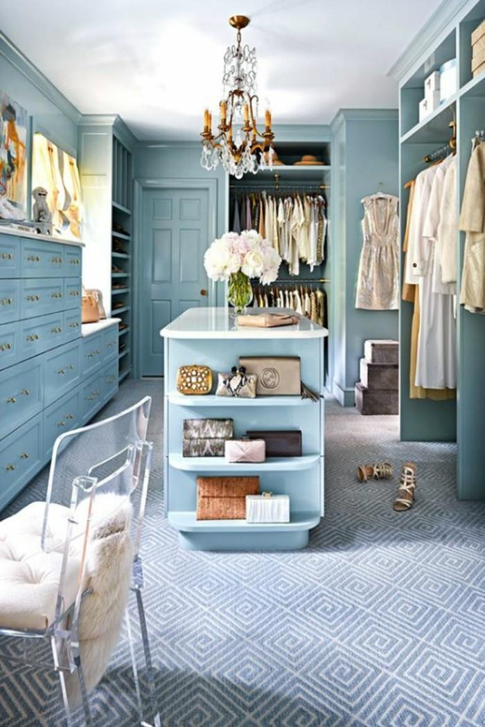 ankleidezimmer-einrichten-blauer-begehbarer-kleiderschrank-goldener-kronleuchter-mit-kristallen-kleider-weise-blumen