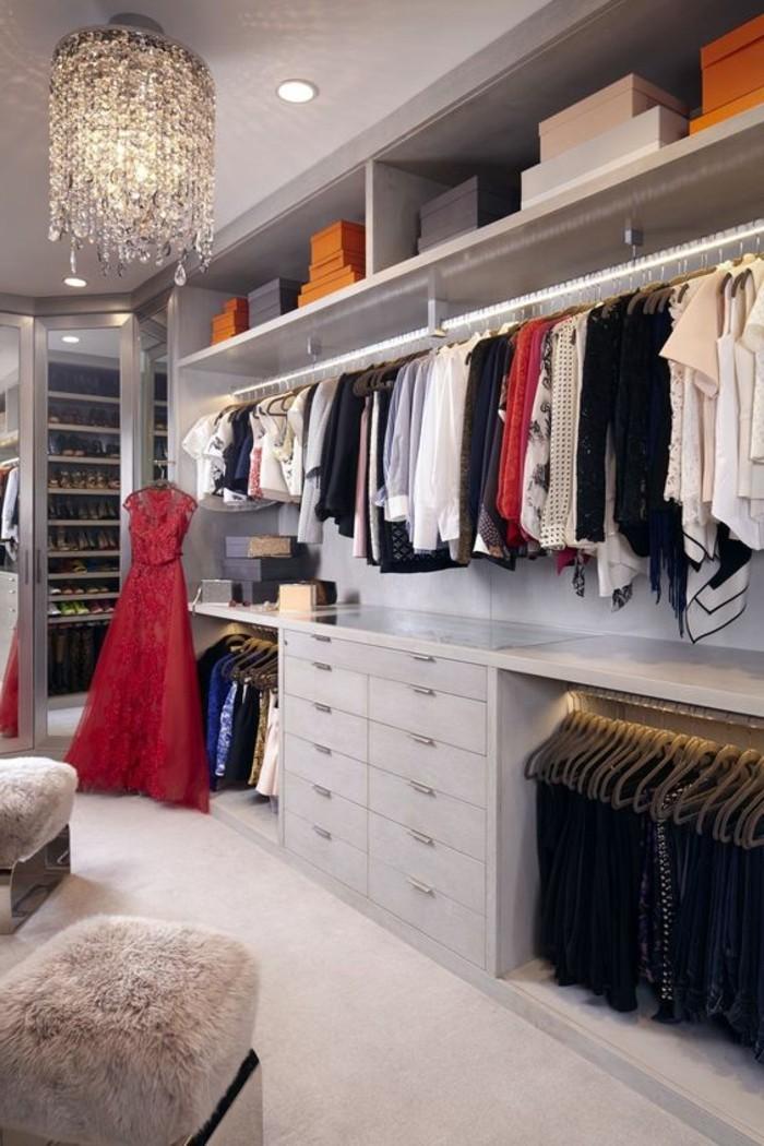 ankleidezimmer-einrichten-grauer-begehbarer-kleiderschrank-rotes-abendkleid-kleider-kronleuchter-aus-kristall
