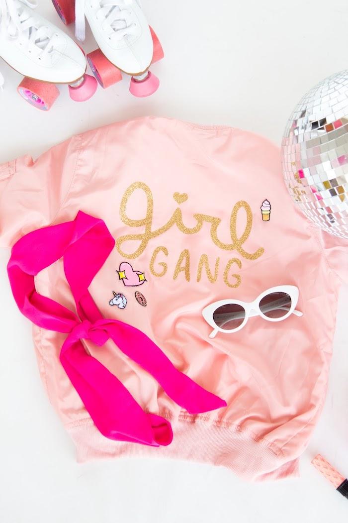 Rosafarbene Jacke mit goldener Aufschrift, Girl Gang, Retro Sonnenbrille und violetter Schal