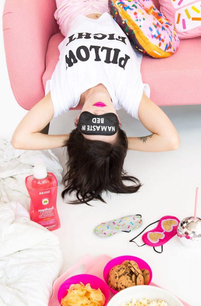 Schwarze Schlafmaske mit weißer Aufschrift, Namaste in Bed, Schüsseln voller Leckereien, Frau mit weißem Shirt und rosa Hose