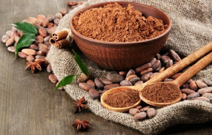 vegane-rezepte-kakao-zimt-kakaobohnen-schuessel-loeffel-auf-dem-tisch-gruene-blaetter