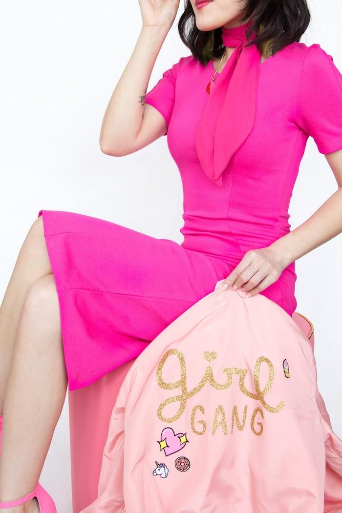 Violettes Kleid mit kurzen Ärmeln, violetter Schal, rosafarbene Jacke mit Aufschrift Girl Gang