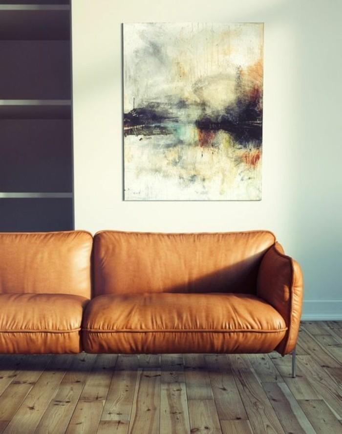 simpel-eingerichtetes-wohnzimmer-leinwand-helle-farben-dunkler-regal-ledercouch-holzboden