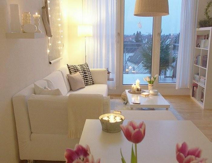 wohnzimmer-gestaltung-und-rosige-tulpen-neben-dem-weisen-sofa