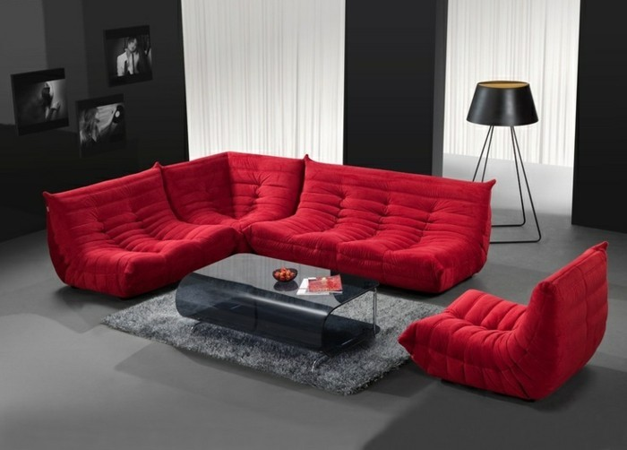 1sessel-rot-moderner-glastisch-grauer-plueschteppich-stehlampe-schwarze-wand-grauer-boden