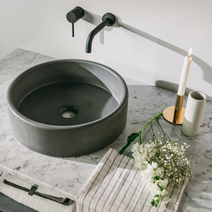 bbadezimmer dekorieren, runder grauer waschbecken, schwarzer hahn, weiße kerze, goldener kerzenständer, marmorplatte