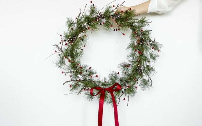 bastelideen weihnachten kreative deko machen hand hält grünen kranz weihnachtskranz selber basteln ideen anleitung