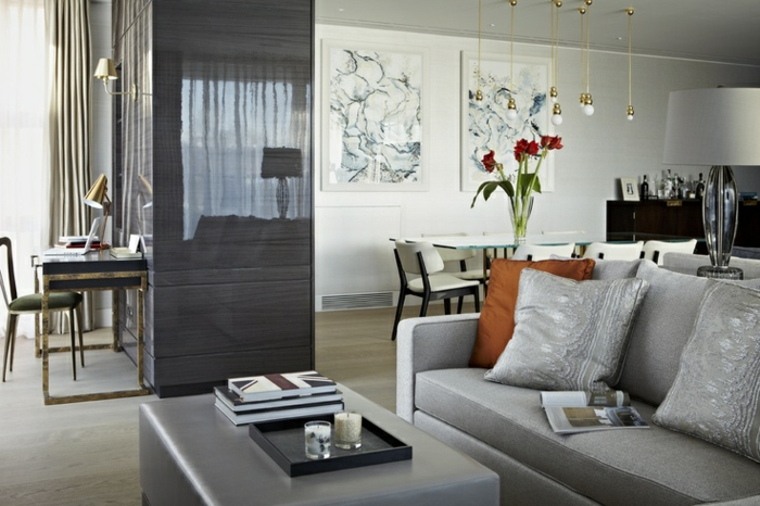 danish-design-moebel-daenische-moebel-plueschsofa-lederhocker-holzboden-silberne-kissen-indirektes-licht-uebergang-zum-wohnzimmer