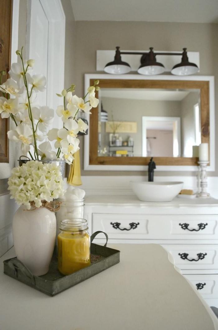 deko für badezimmer, badspiegel mit holzrahmen, baddeko ideen, vase mit weißen blumen, schrank im vintage stil