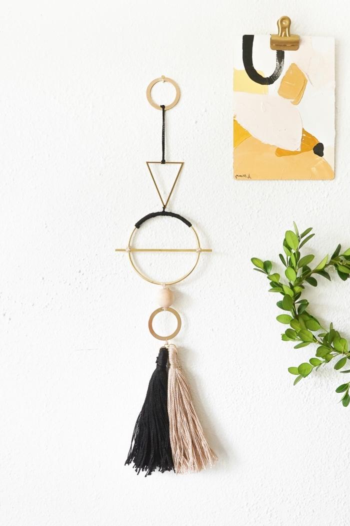 hängende dek aus metallenen elementen, schwarzem und beige garn, deko ideen selbst machen