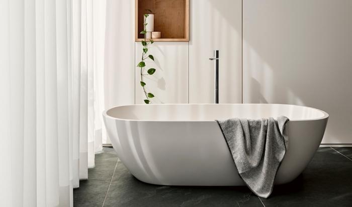 designer badezimmer einrichtung, freistehende badewanne in minimalsitischem stil, schwarze bodenfliesen, weiße gardinen