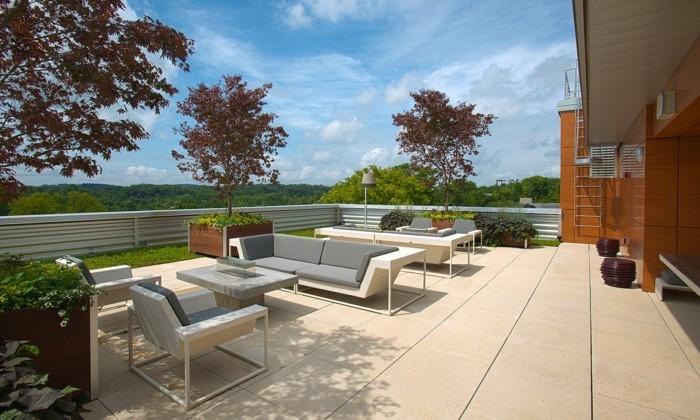 eine-moderne-terrasse-mi-hellbraunen-terrassenfliesen-und-mobiliar