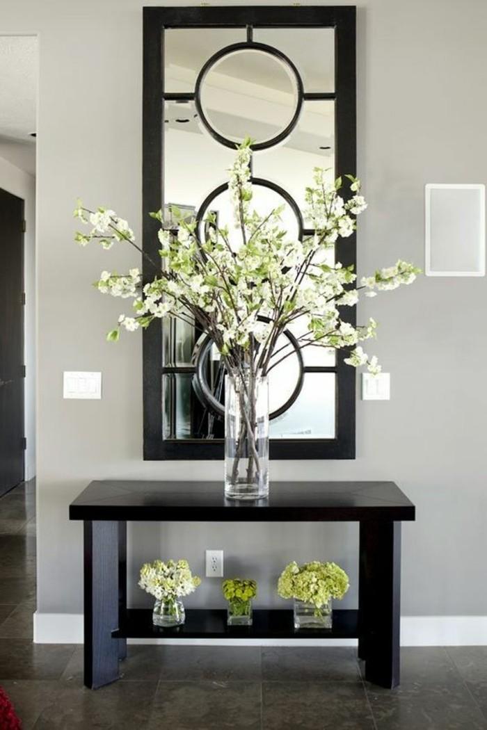 flur-einrichten-deko-flur-schwarzer-tisch-eckiger-spiegel-mit-schwarzem-rahmen-weise-blumen