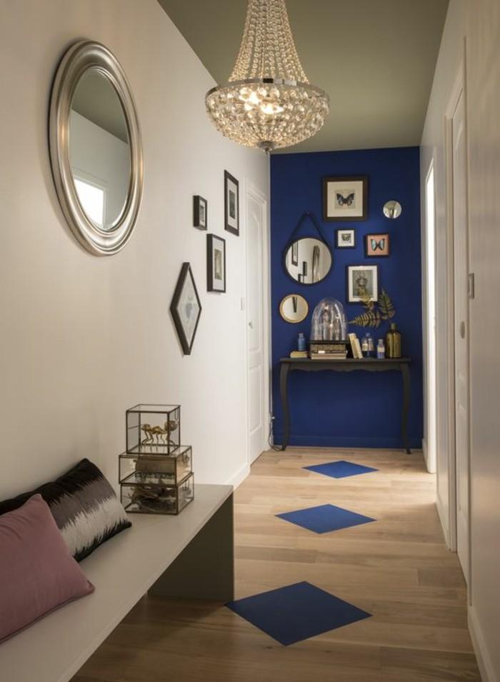 flur-einrichten-farbgestaltung-flur-in-beige-und-bleu-rundem-spiegel-kronleuchter-aus-kristall-fotos-boden-aus-holz