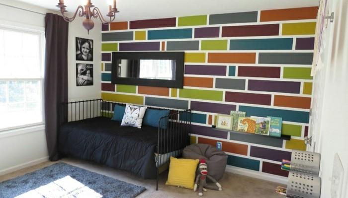 geometrische-formen-kinderzimmer-wandgestaltung-plueschteppich-schwarze-schlafdecke-spielzeuge-hocker-familienfotos