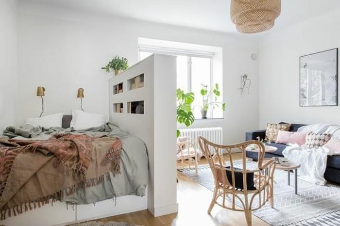 geschlossener-regal-raumtrenner-regale-als-raumtrenner-regal-raumtrenner-doppelbett-bunte-schlafdecken-holzstuhl-musterteppich-holzboden-kleiner-kaffeetisch