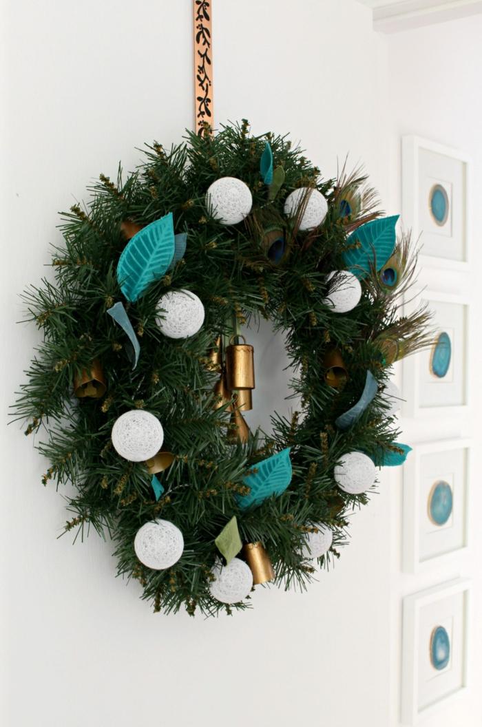 grünen weihnachtskranz selber basteln dekoriert mit weißen weihnachtskugeln blaue federn kranz aufgehängt an tüt
