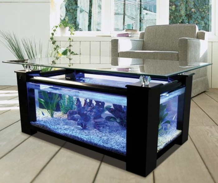 groser-viereckiger-aquarium-blaues-wasser-steine-aquariumtisch-wohnzimmer-holzboden-weicher-sessel