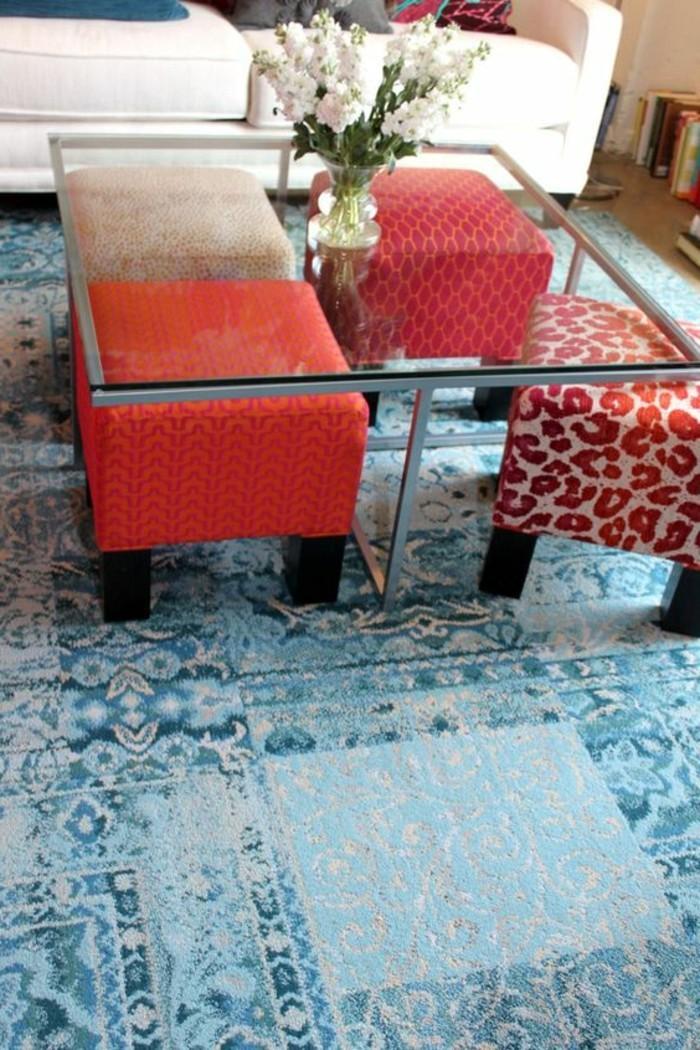 kleines-wohnzimmer-tisch-aus-glas-hocker-blumen-blauer-retro-teppich