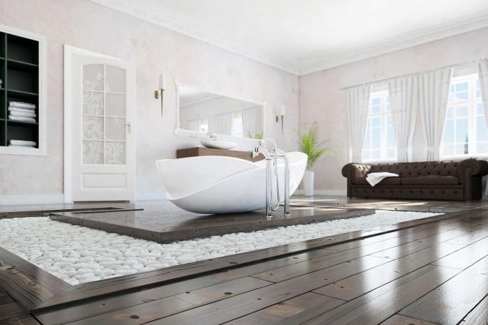 moderne bäder, boden aus holz, pfad mit weißen steinchehn, designer badewanne, brauner ledersofa