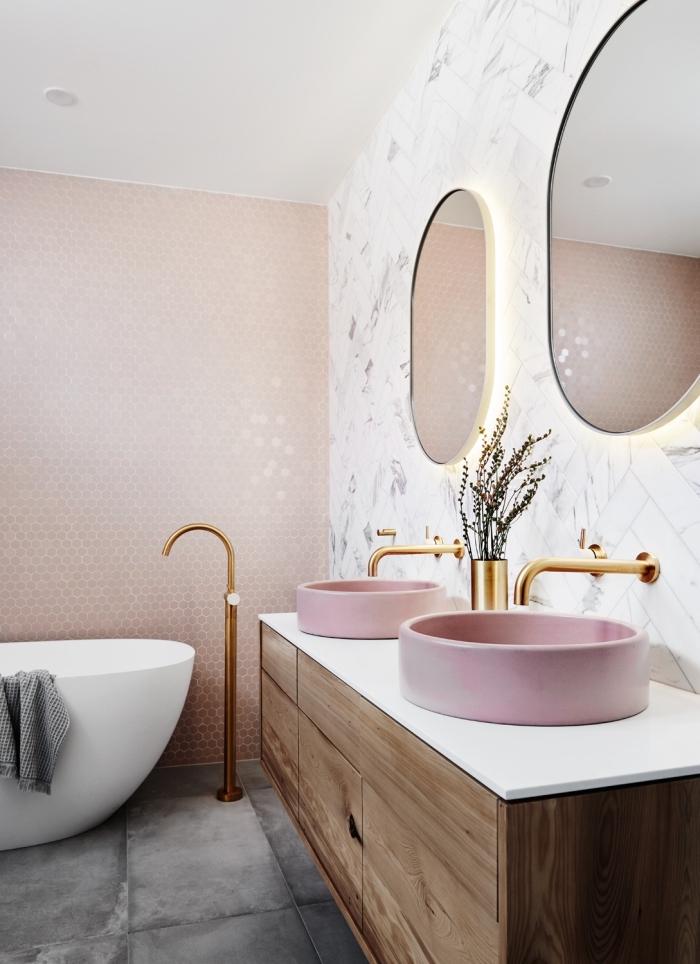 moderne bäder, badgestaltung in weiß und rosegold, rosa waschbecken mit unterschrank aus golt, ovale spiegel mit beleuchtung