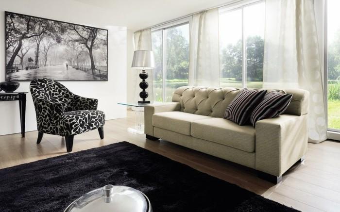 moderne-sessel-in-schwarz-und-weiss-pflanzenmotive-weisse-couch-schwarzer-plueschteppich-glastisch-lange-transparante-gardinen-fenster-bis-zum-boden