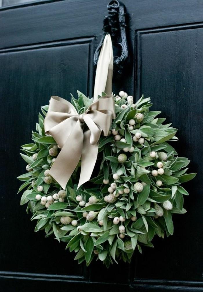 moderne-weihnachtsdeko-gruene-zweigen-beige-schleife-aus-seide-schwarzer-tuer