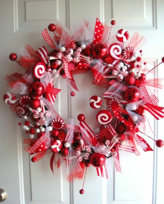 moderne-weihnachtsdeko-weisse-tuer-suessigkeiten-schleifen-rote-weihnachtskugeln