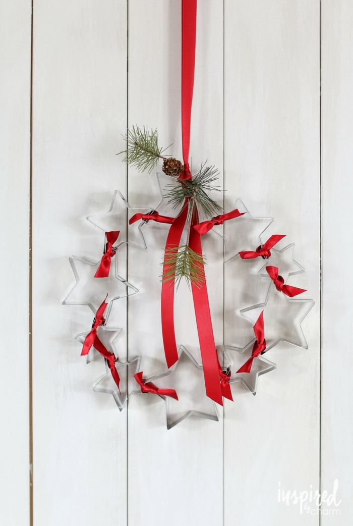 originelle bastelideen weihnachtskranz basteln aus ausstechformen in sternform dekoriert mit rotem band tannenzweigen und tannenzapfen