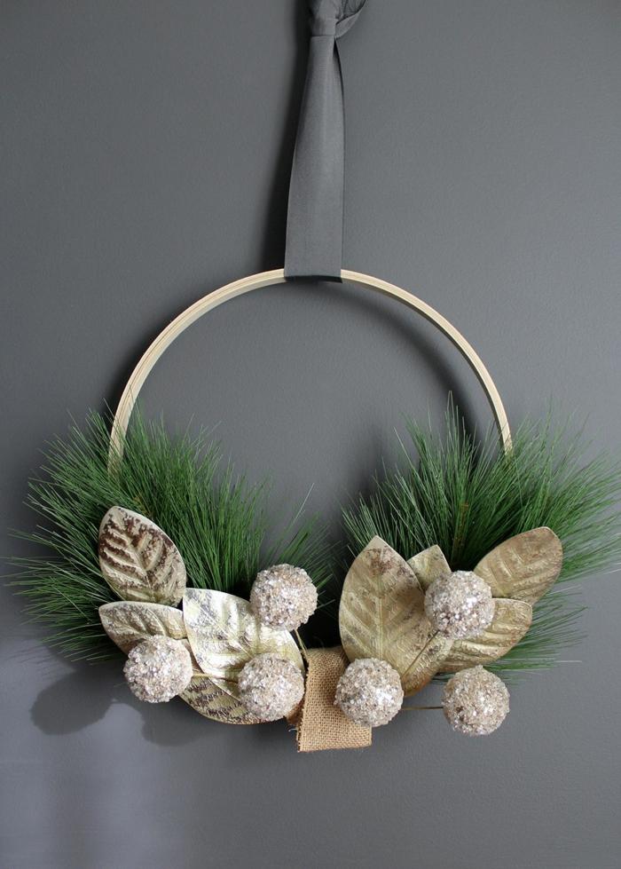 schönen weihnachtskranz selber machen mit goldenen blättern tannenzweigen weihnachtskugeln aufgehängter kranz originelle bastelideen