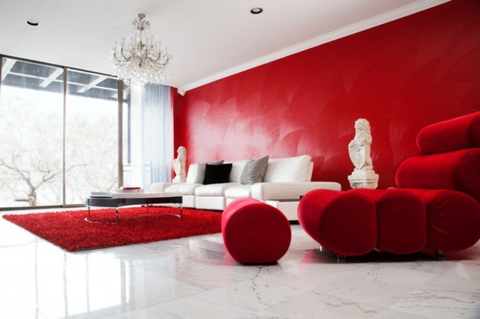 sessel-rot-hocker-rot-polstersessel-roter-plueschteppich-weisse-bodenfliesen-rote-wand-kronleuchter-aus-kristall