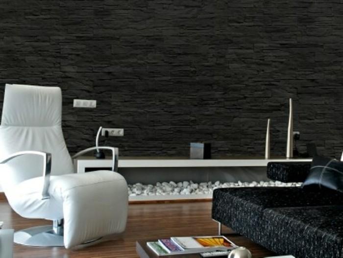 sessel-weiss-holzboden-schwarze-couch-steinwand-holztisch-buecher-ledersessel-steinendeko