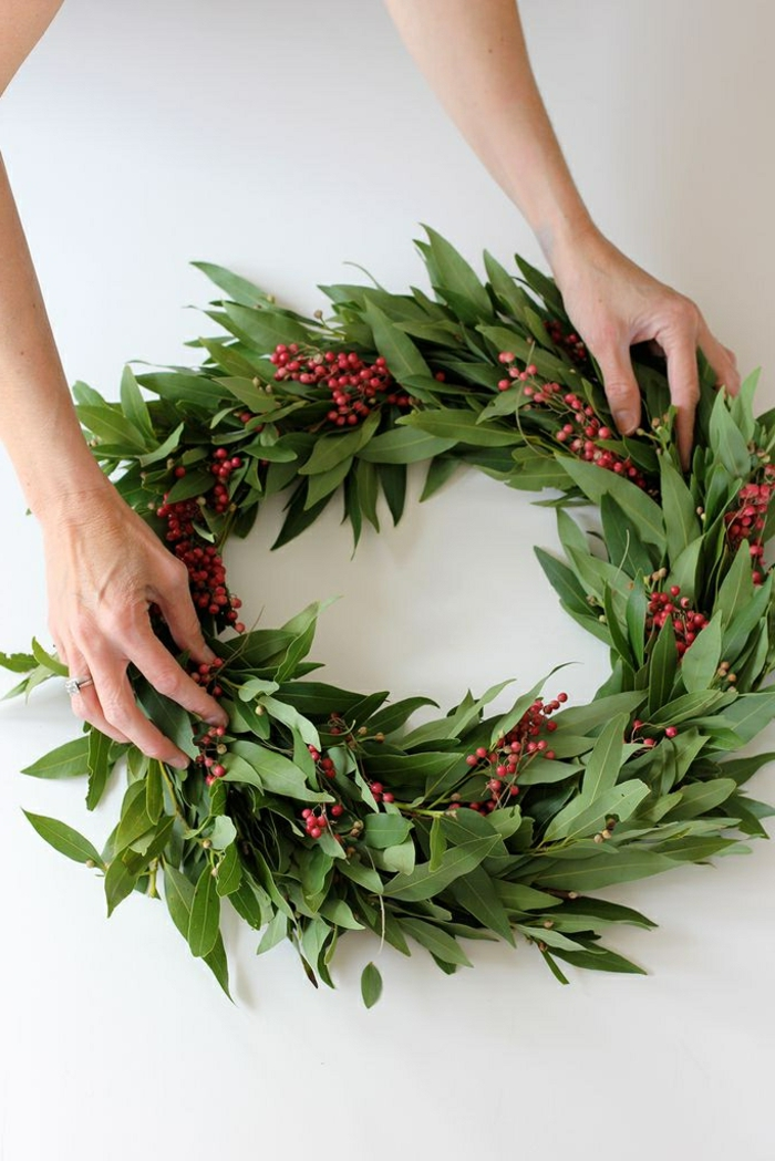 simpler weihnachtskranz tür aus loorbeerblätter und blüten person bastelt kranz minimalistische deko weihnachten