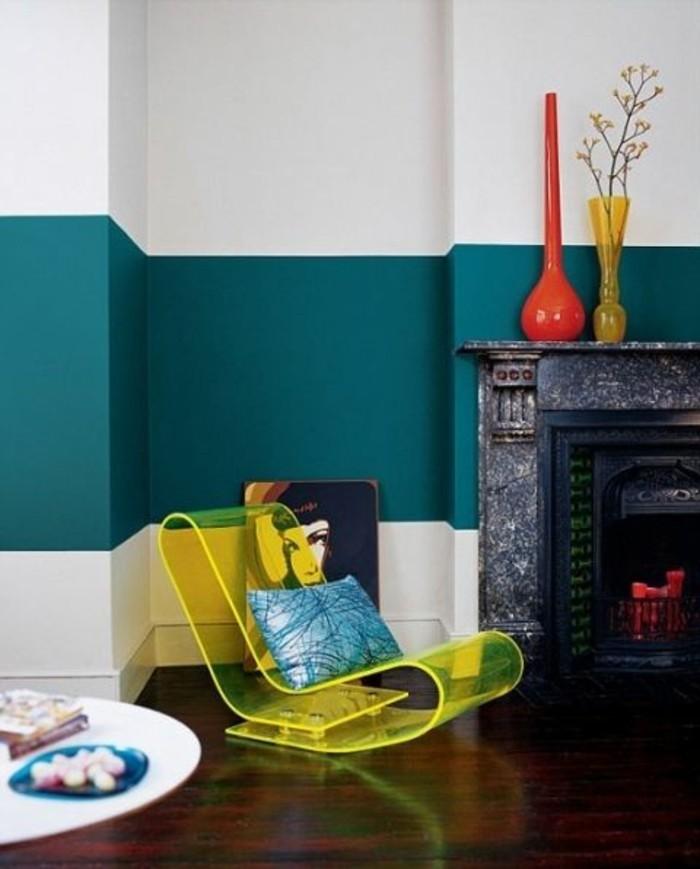 streifen-streichen-wand-wohnzimmer-weiss-blaue-wand-holzboden-plastikstuhl-blaue-gestreifte-kisse-weisser-rundtisch-feuerstelle-blumenvasen