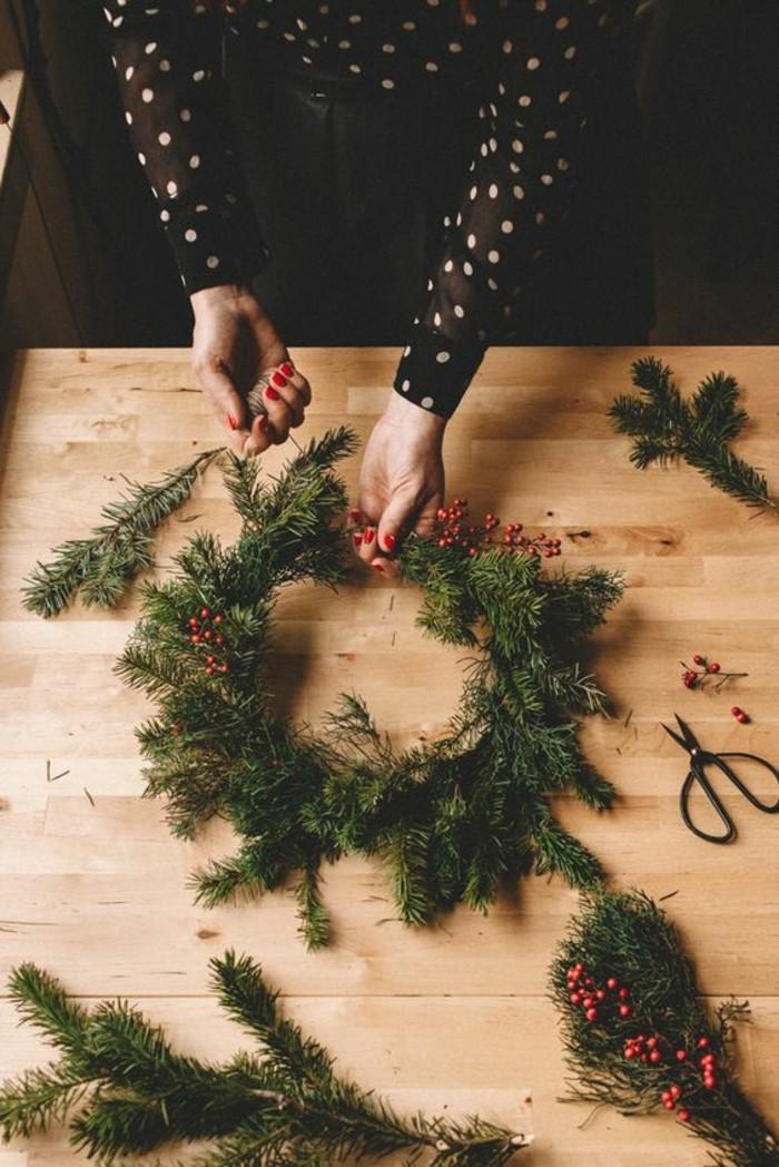 tuerkraenze-weihnachten-aus-gruenen-zweigen-hoelzerner-tisch-roter-nagellack