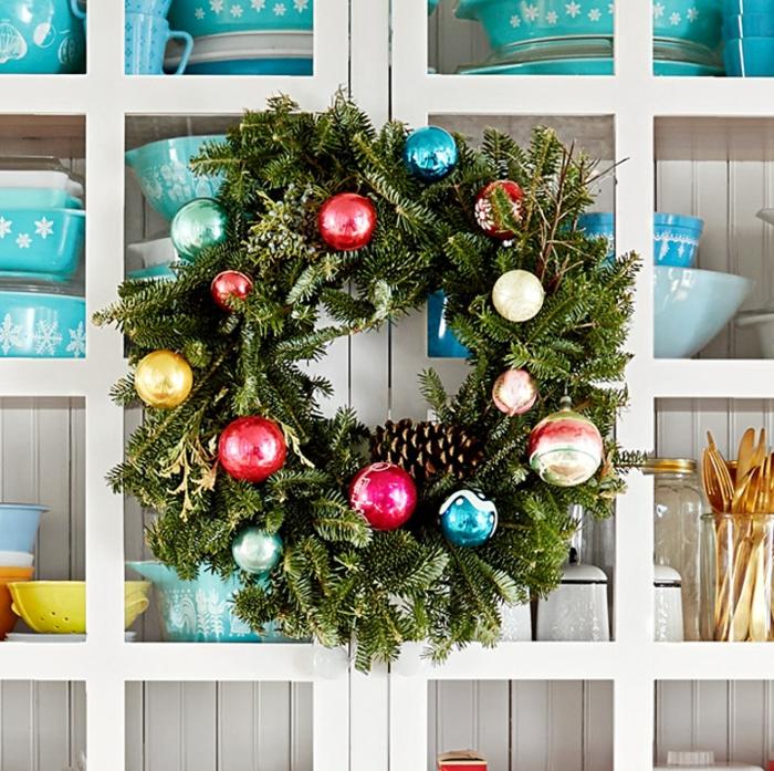 traditionellen kranz weihnachten inspiration grüner weihnachtskranz dekoriert mit bunten weihnachtskugeln und tannenzapfen weißer küchenschrank