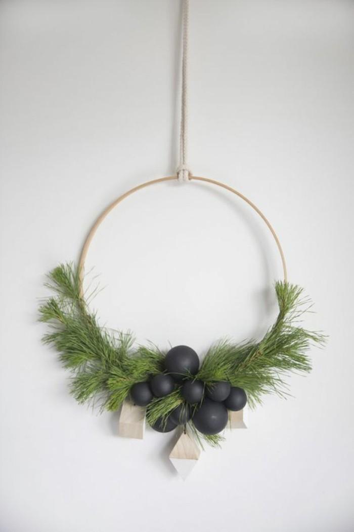 weihnachtskranz-basteln-gruenen-zweigen-weisse-wand-schwarzen-weihnachtskugeln
