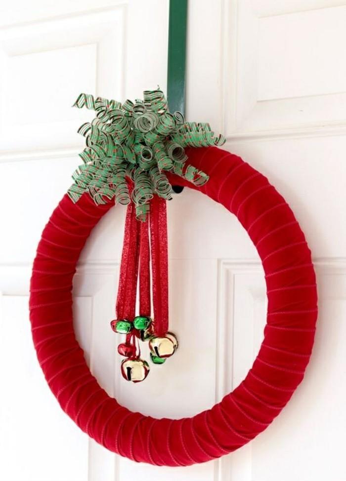 weihnachtskranz-basteln-roter-stoff-gloecken-gruene-schleife-weisse-tuer