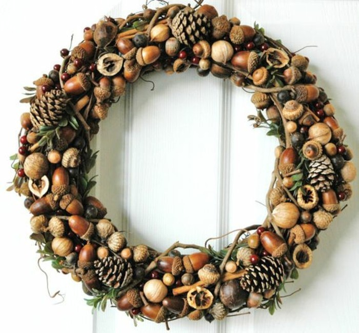 weihnachtskranz-basteln-zapfen-aeste-eichel-wallnuesse-weisse-tuer