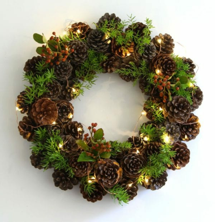 weihnachtskranz selber machen aus tannenzweigen und grünen zweigen dekoriert mit kleinen lichter originelle bastelideen