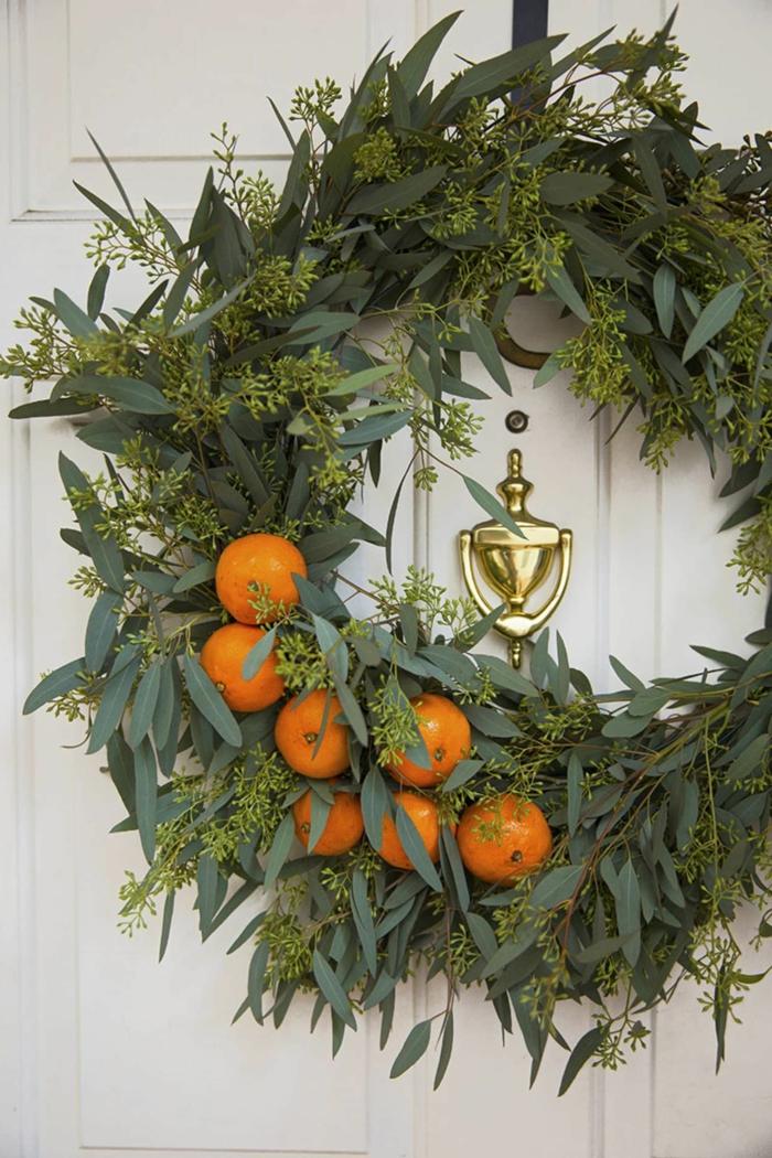 weihnachtskranz tür inspiration grüner kranz dekoriert mit mandarinen weiße eingangstür