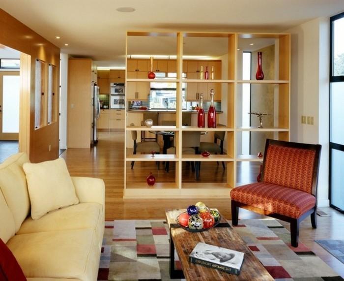 wohnungseinrichtung-trennwand-regal-paravent-offener-bucherregal-raumteiler-weiße-couch-musterteppich-holztisch-übergang-zum-esszimmer