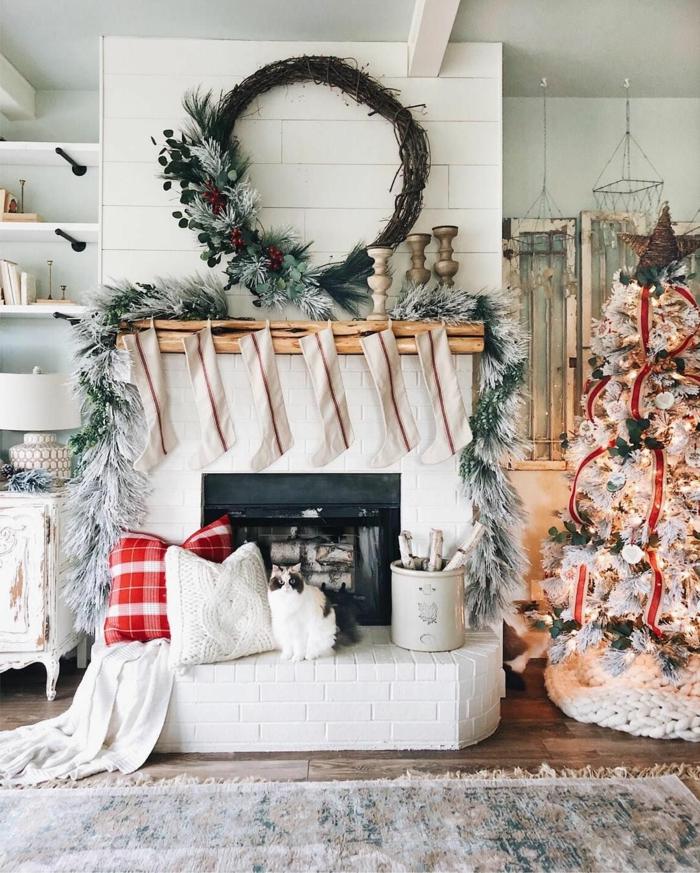 wohnzimmer dekorieren weihnachten weißer dekorierter tannenbaum nikolausstiefel am kamin weihnachtskranz selber machen