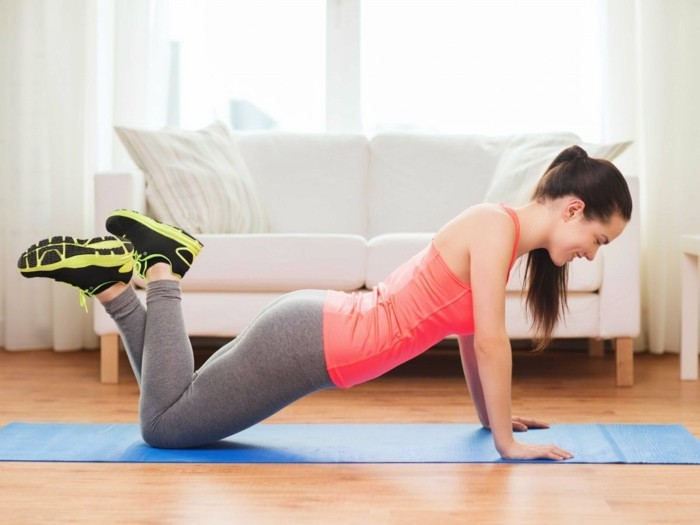 13workout-fuer-zuhause-uebungen-arm-yoga-mate-blau-weisse-couch-parkettboden