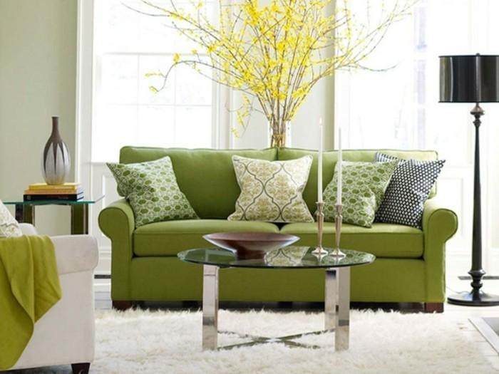 1farbgestaltung-wohnzimmer-couch-in-gruen-kissen-musterbezuege-gelbe-pflanze-weisser-teppich-runder-glastisch-kerzen-sessel-weiss-stehlampe-vase