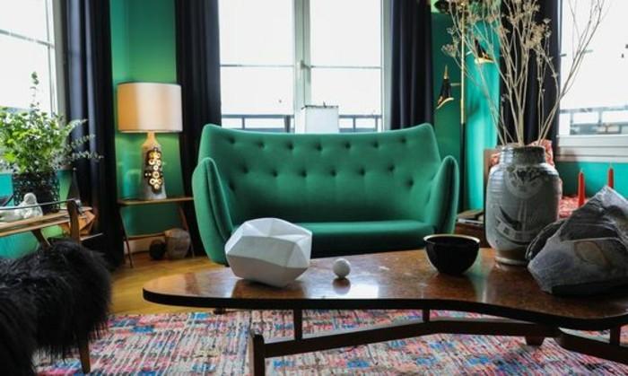 3feng-shui-farben-farbgestaltung-wohnzimmer-gruene-couch-gruene-wand-schwarze-gardinen-bunter-teppich-ovaler-holztisch-tischdeko-vase-indirektes-licht